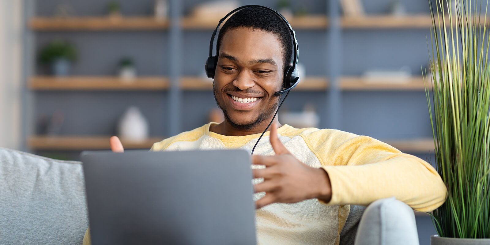 Student with headphones in front of laptop computer, engaging in conversation