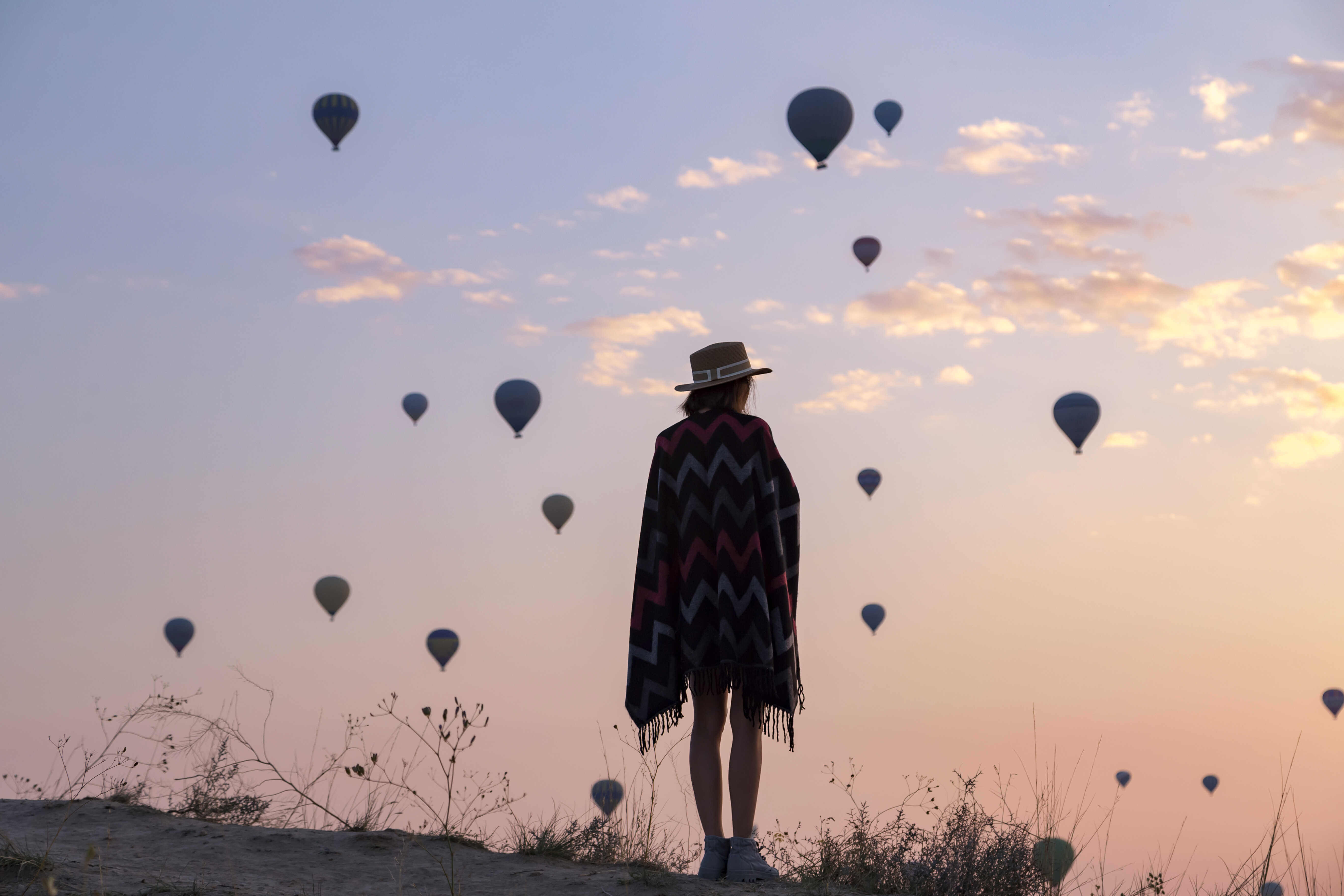 Young woman looking out at hot air balloons in the sky