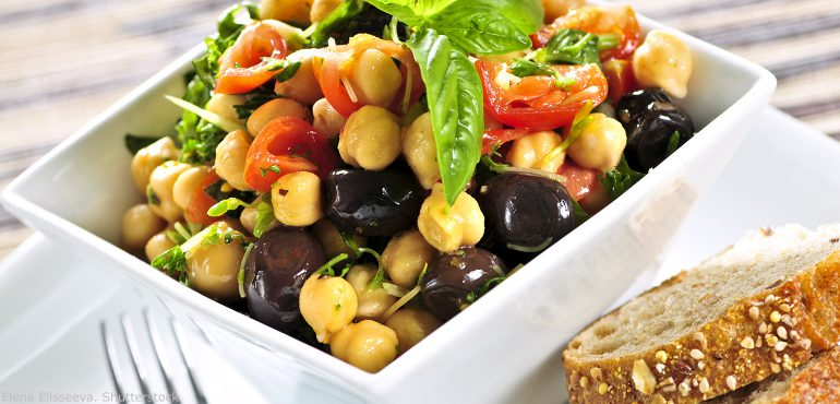 A bowl of bean salad with tomatoes and herbs and a side of bread