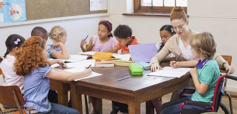 A group of elementary students some with EBD sitting around a table while writing on pieces of paper