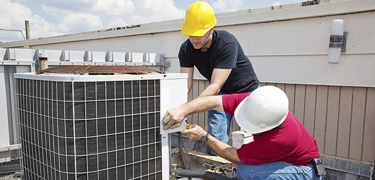 Men working on air conditioning unit