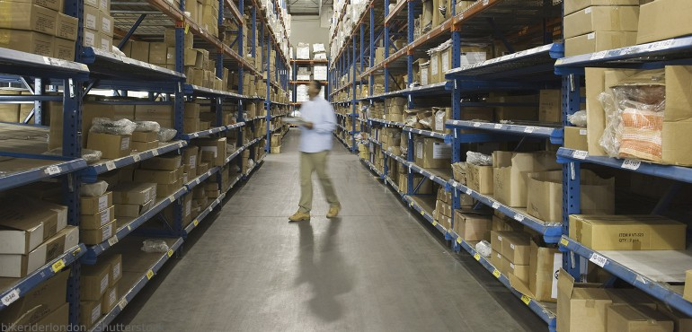 Adult male standing near boxes in a distribution center