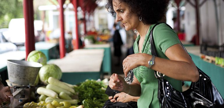 Adult woman shopping for fresh vegetables at outdoor market