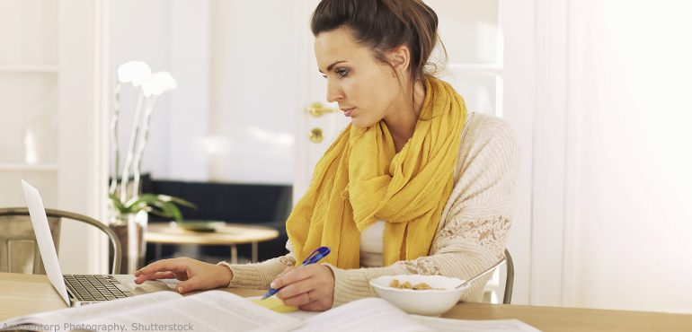 Adult woman sitting at kitchen table studying with laptop and books