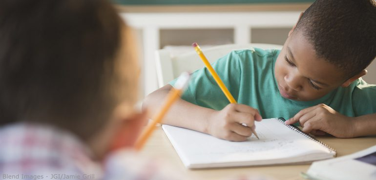 African American boy writing in a notebook while sitting in a classroom