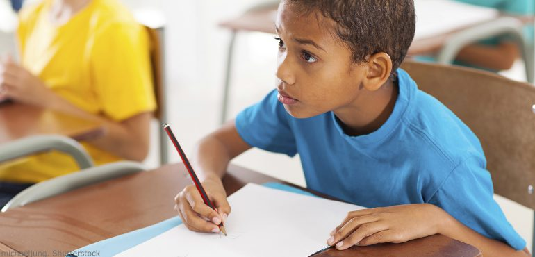 African American male elementary student sitting at a desk drawing math graphs