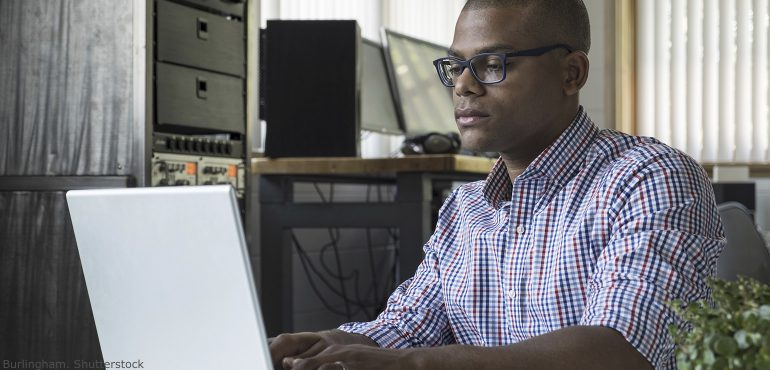 African American male in his home at a desk working at a laptop