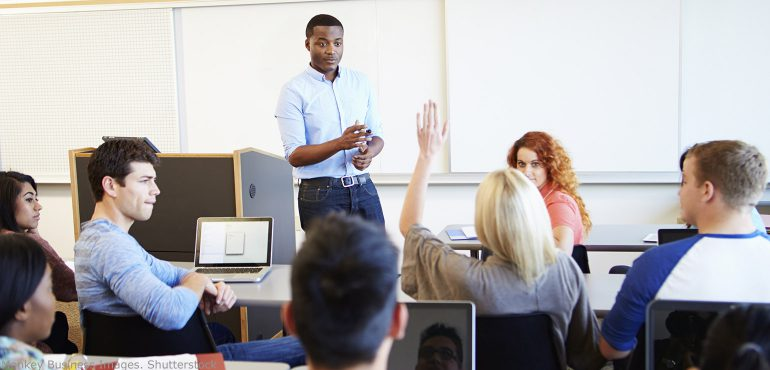 African American professor talking with students in the classroom