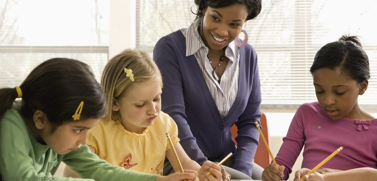 African American teacher working with three female elementary students