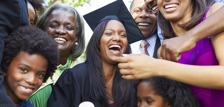 African American woman graduating from college and smiling with her family
