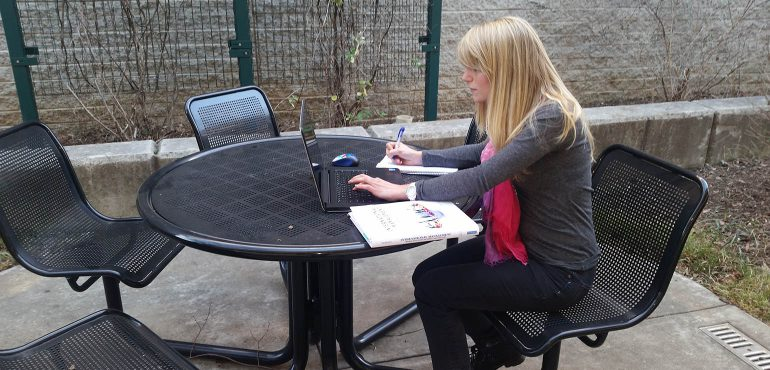 Female students at a table outside studying with computer and textbook