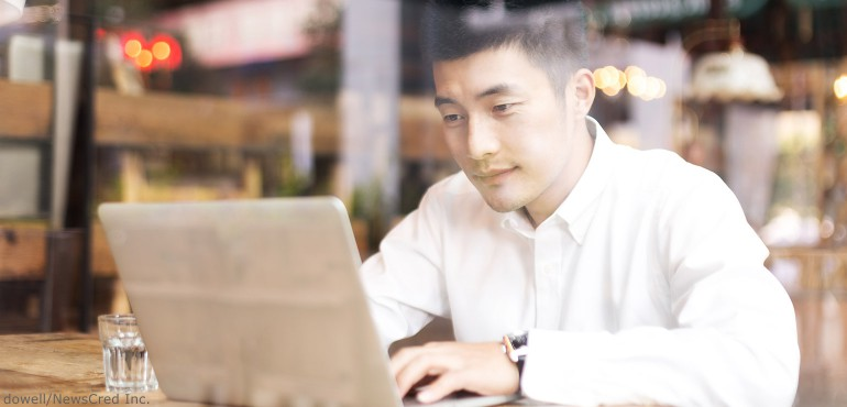 Asian male sitting in a restaurant at a table looking at a laptop computer