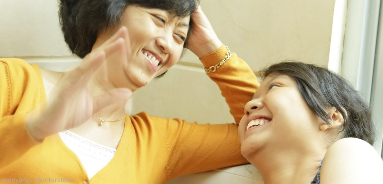 Asian mother and daughter laughing while sitting on a couch