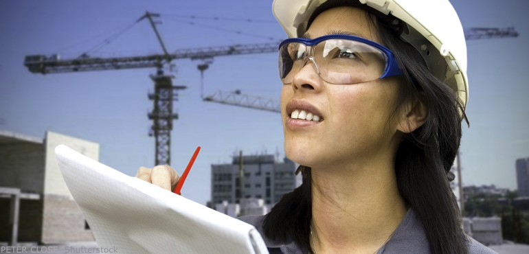 Asian woman construction worker standing in front of an industrial crane