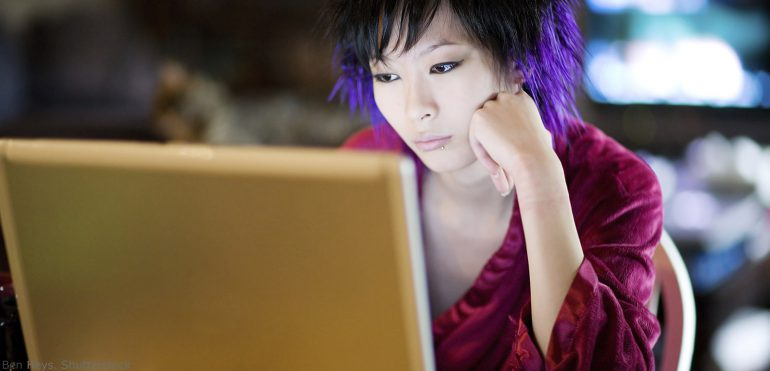 Asian woman sitting at a desk in her home looking at a laptop
