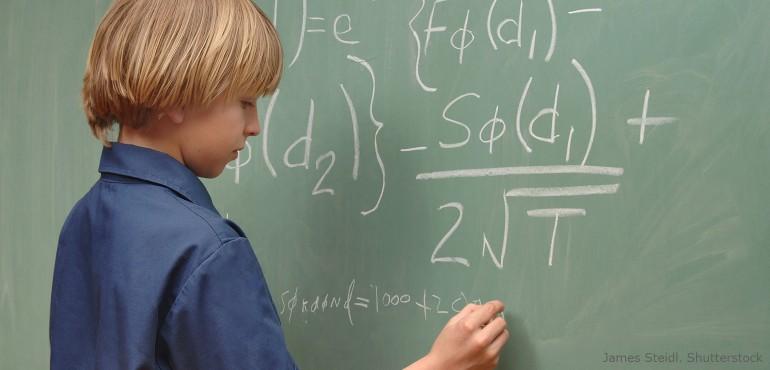 Boy solving advanced math problem on chalk board