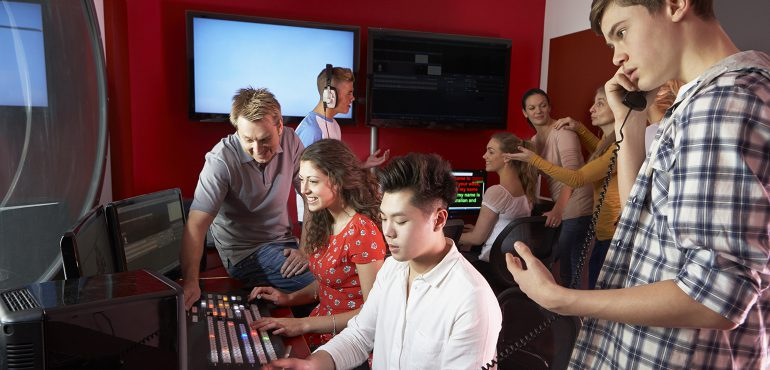 Group Of Media Students Working In Film Editing Class