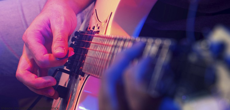 Close up view of hands playing an electric guitar