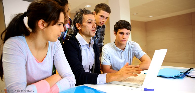 College professor and students gathered around a laptop