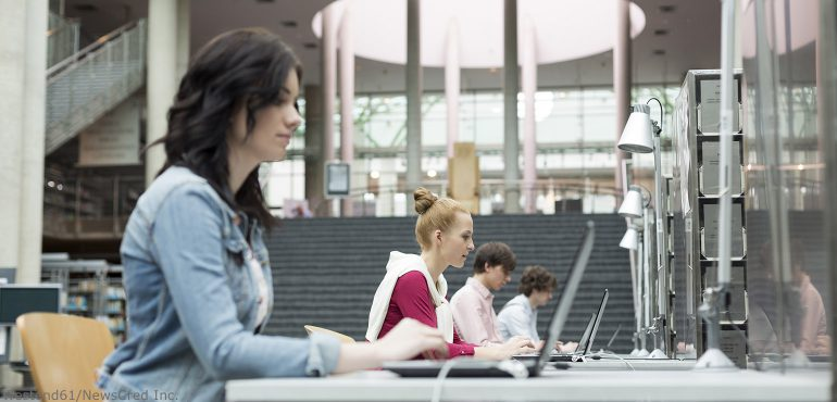 College students sitting at desks using laptops in a library
