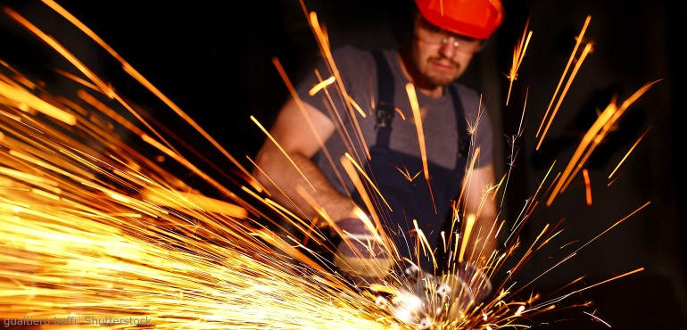 Construction worker cutting metal with sparks flying