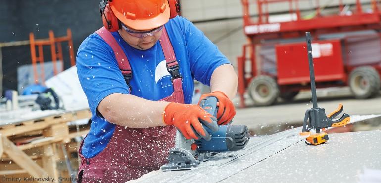 Construction worker cutting a sheet of plastics