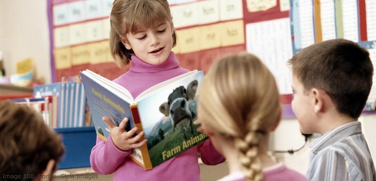 Elementary school girl reading to classmates