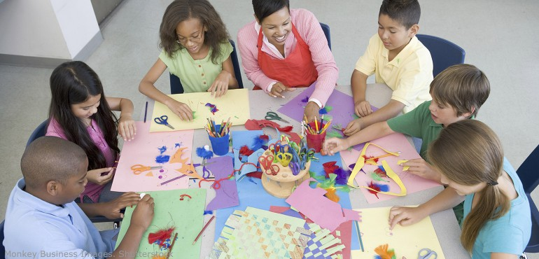 Elementary students sitting around a large table creating art projects