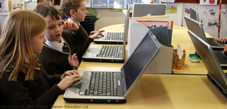 Elementary students working on laptop computers