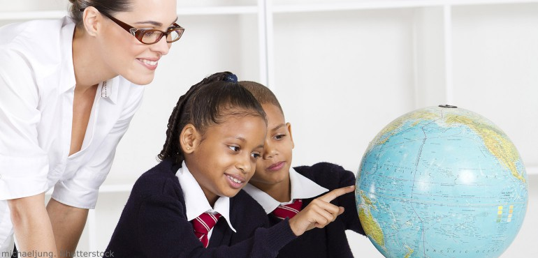 Elementary teacher and students looking at a globe in a classroom