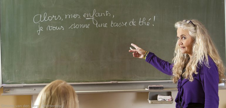 Female college professor pointing at green chalkboard and lecturing