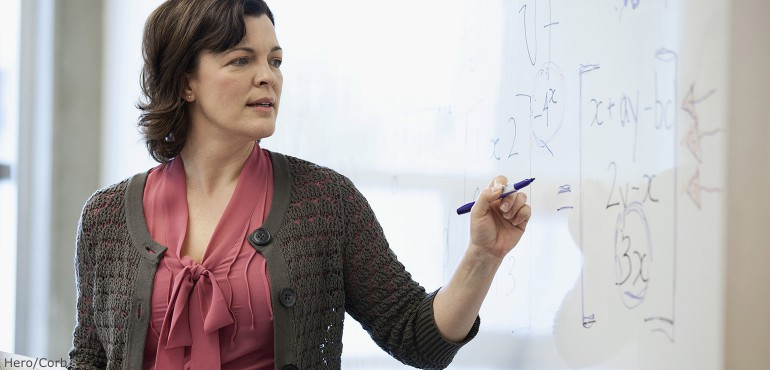 PSM female college professor writing math equations on a white board