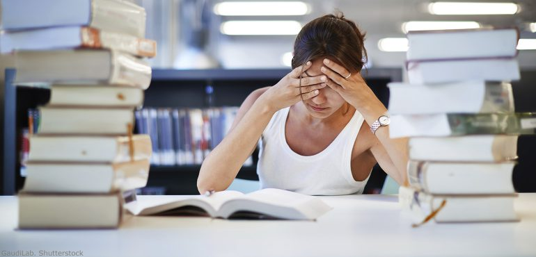 Female college student sitting at a desk with two piles of books and her hands over her face
