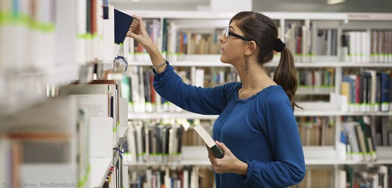 Female college student taking a book off of a shelf in a library