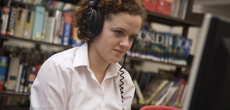 Female high school student sitting in library wearing a headset looking at computer screen
