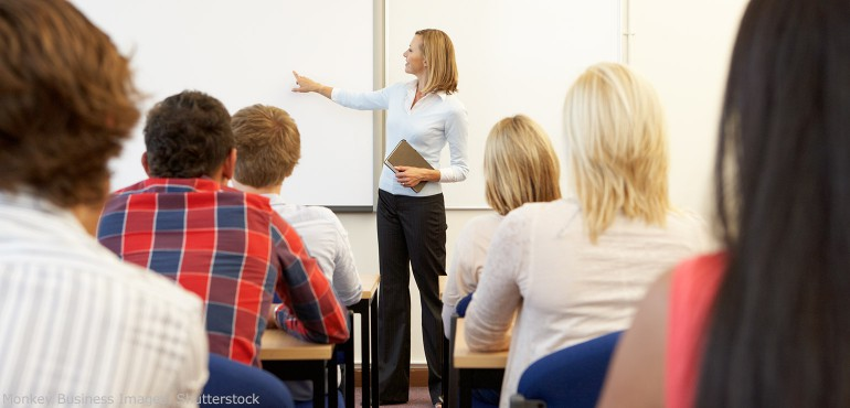 Female professor lecturing in classroom pointing a white board