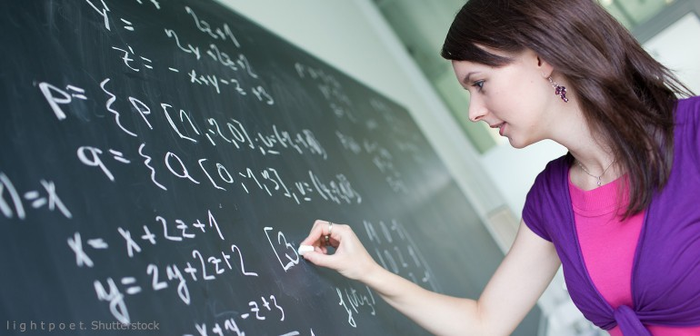 Female student solving math problem on chalkboard