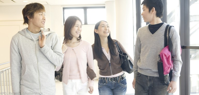 Four Asian college students walking down the hallway