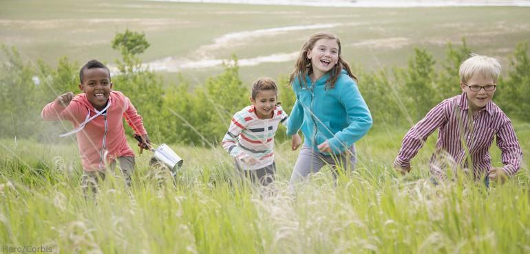 Four children running in an open field filled with tall grass