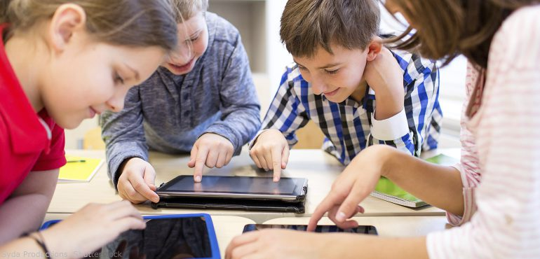 Four elementary school students using digital tablets in a classroom