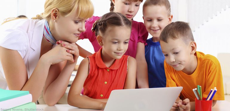 Four elementary students and a teacher looking at a laptop computer