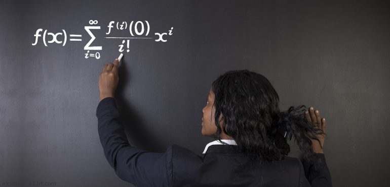 African American female student writing a math equation on chalkboard