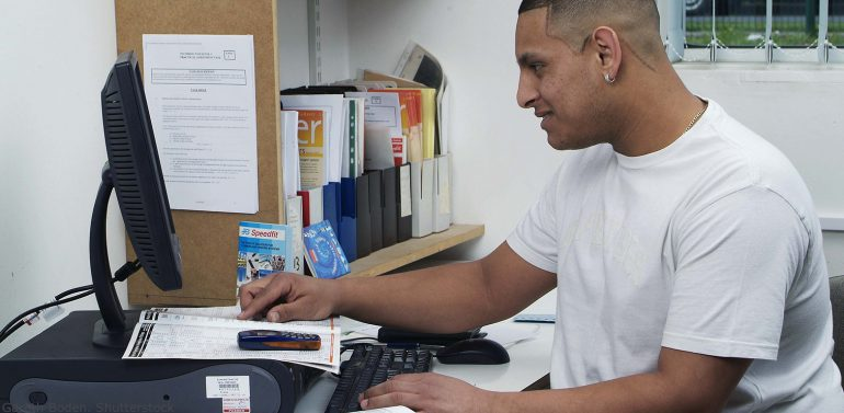 Hispanic adult male working at a desk with a computer and manuals