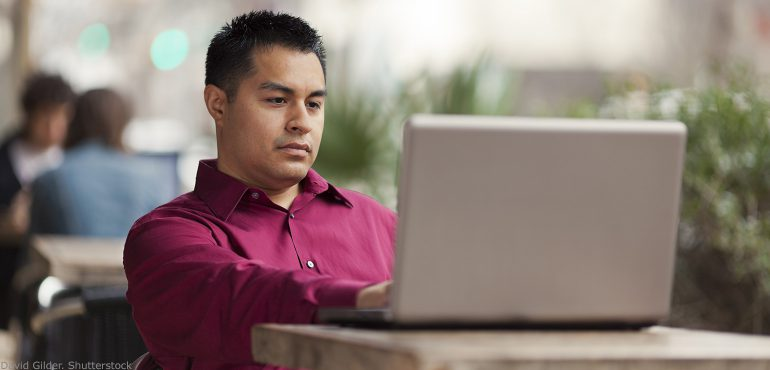 Latino male sitting in an outdoor cafe table looking at a laptop computer