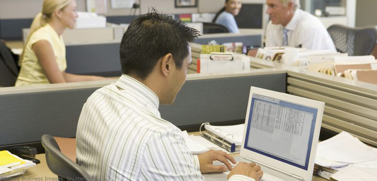 Latino male working on a laptop in an open office setting