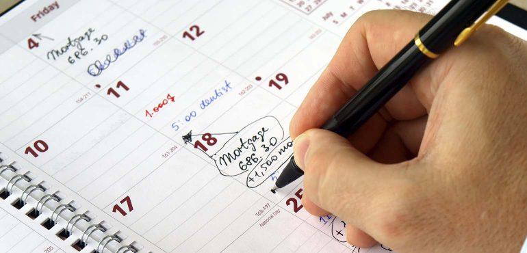 student writing in deadlines on calendar