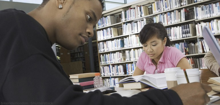 Male African American student and a female Asian student studying in a library