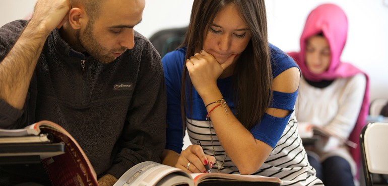Male and female students looking at a workbook