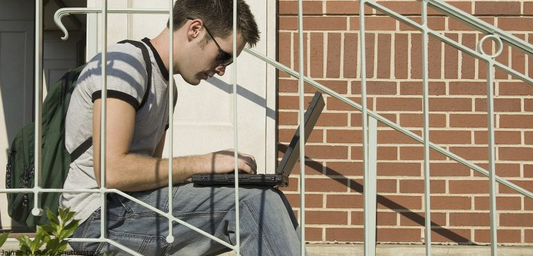 Male college student sitting on outside staircase looking at a laptop