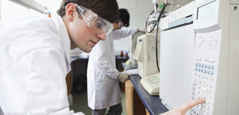 Male college student working in a laboratory pushing buttons on a machine